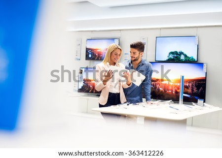 Lovely couple is at store and they are looking for a new mobile, tablet or TV at catalog. Shallow depth of field.