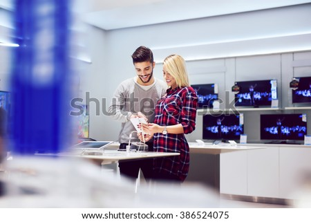 Lovely couple is at store and they are looking for a new tablet. Shallow depth of field.