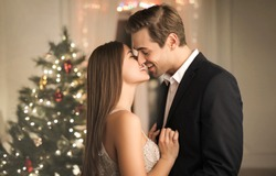 Lovely couple kissing at home, while celebrating New Year's Eve