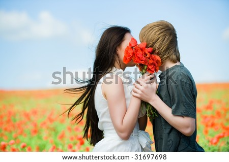 Lovely couple kissing in the poppy field