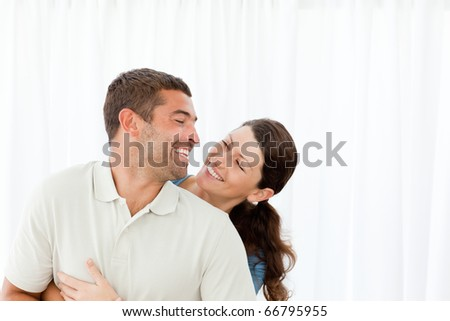 Lovely couple laughing together in the living room at home