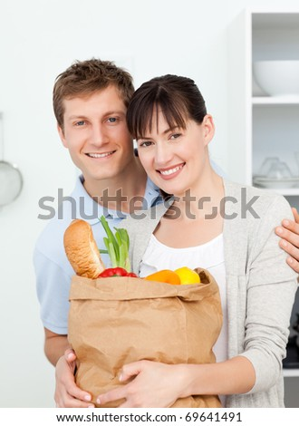 Lovely couple looking at the camera with their shopping bags at home