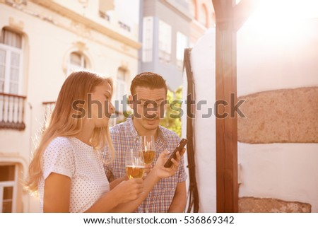 Lovely couple looking at the cellphone with interest while enjoying some beers with bright sunshine behind them #536869342