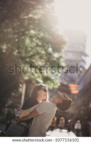 Lovely couple looking each other and enjoying a nice summer day in the city street oudoors. Beautiful couple having lovely romantic moments outdoors. #1077156101