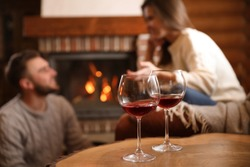Lovely couple near fireplace at home, focus on glasses with wine. Winter vacation
