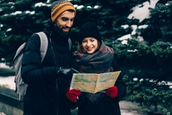 Lovely couple of tourists agreeing on traveling route, adult man showing woman location with finger, using map, both smiling and standing on background of snowy winter city