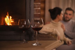 Lovely couple resting near fireplace, focus on glasses with red wine