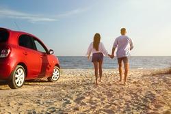 Lovely couple running on sandy beach. Summer trip