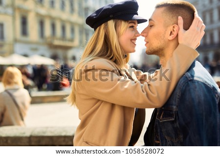 Lovely couple stand on city landscape and hug each other with sun on background #1058528072