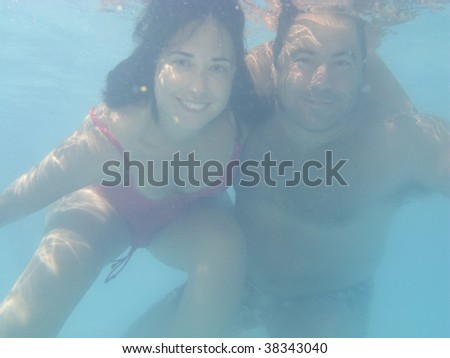 Lovely couple underwater on a swimmingpool, underwater photo