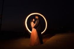 Lovely Couple wearing gown and suit western outfits holding and looking at each other in night with ring of fire spark long exposure , relationship and love concept