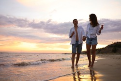 Lovely couple with glasses of wine walking on beach at sunset. Space for text