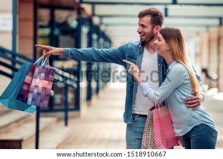 Lovely couple with shopping bags. Concept of consumerism and happiness.