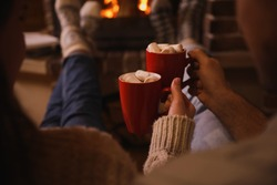 Lovely couple with sweet cocoa near fireplace indoors, closeup