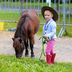Lovely cowgirl feeding with grass little pony horse in the farm. Pretty preschooler girl wearing cowboy hat playing with animals outdoors on sunny day.