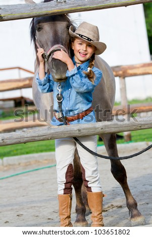 Lovely cowgirl with horse on a ranch