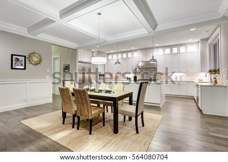 Photo of Lovely craftsman style dining and kitchen room interior with coffered cealing over rustic wooden dining table surrounded by wicker chairs. Northwest, USA