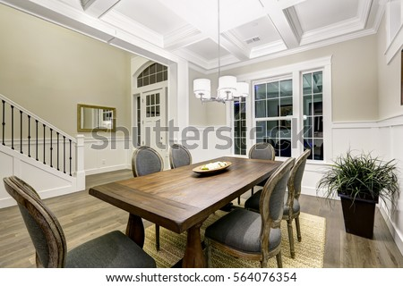 Photo of Lovely craftsman style dining room with coffered cealing over wooden dining table surrounded by grey chairs atop sisal rug. Northwest, USA