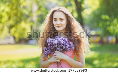 Lovely curly girl with a bouquet of lilacs on a sunny summer day, nice smile, good open look
