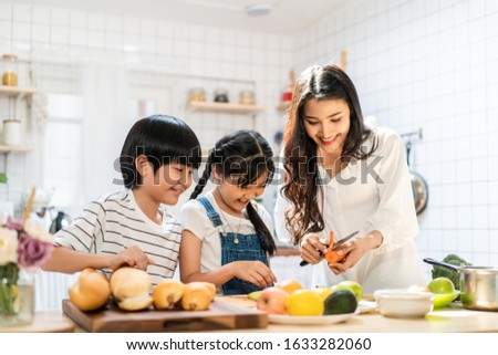 Lovely cute Asian family making food in kitchen at home. Portrait of smiling mother and children standing at cooking counter preparing ingredient for dinner meal. Happy family activity together.