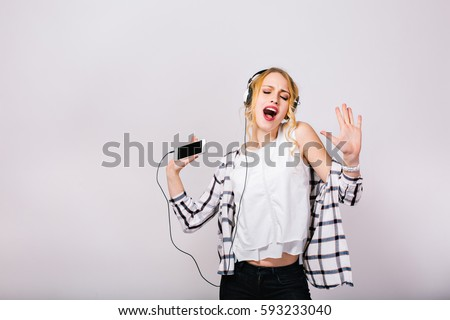 Lovely cute blonde woman enjoying her life, singing and dancing with closed eyes. Mirthful smart girl wearing stylish white blouse with black trousers. Isolated grey background.