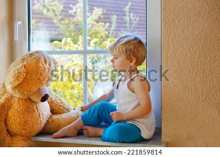 Lovely cute child of two years sitting near window with big toy bear