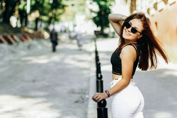 Lovely cute young woman. With long hair wearing black glasses and walking in the city with charming smile during photoshoot.