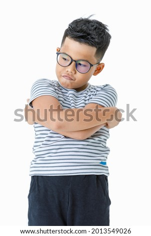 Lovely cutout portrait of pity young Asian boy wearing glasses and casual horizontal striped shirt shrinking and hands covering cheek as afraid of blaming his guilt, fault, and mistake Stock photo ©