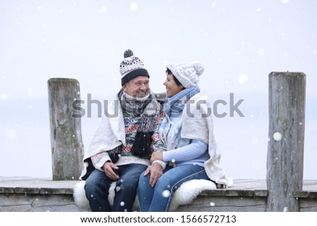 lovely elderly couple enjoy a winter day in warm clothes at the jetty at the lake stock photo