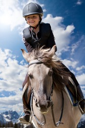 Lovely equestrian - little girl is riding a horse, Dolomites mountain in the background