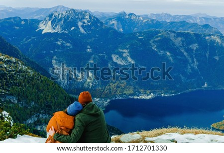 Photo of  Lovely family couple sitting on moutain peak with beautiful background and looking to landscape. Wonderful picture with copy space. Five fingers view point near Hallstatt village in Austria. Valley.