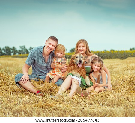 ShutterStock lovely family parents and two daughters with dog in field ...