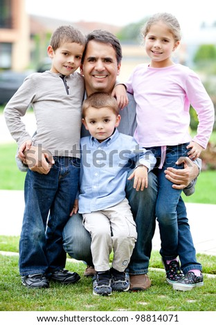 Lovely family portrait of father with his children smiling outdoors