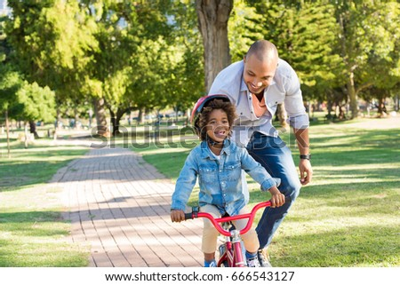 Lovely father teaching son riding bike at park. Happy father helping excited son to ride a bicycle at park. Young smiling black boy wearing bike helmet while learning to ride cycle with his dad.