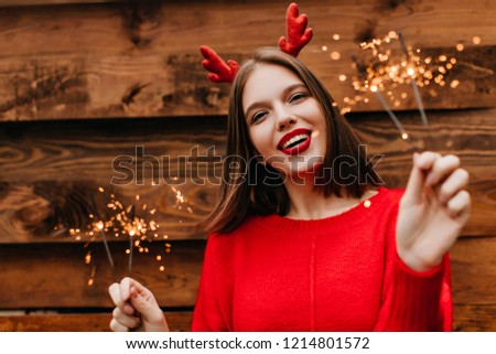 Lovely female model with straight hairstyle holding bengal lights with inspired smile. Cute woman in red sweater preapring for new year. #1214801572