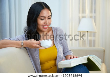 Lovely Filipino female with charming smile enjoying fresh hot drink and reading nice book while sitting on comfortable couch in cozy living room #1203918694