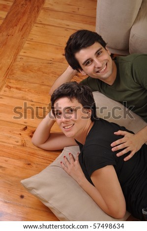 lovely friendship between sister and brother lying and relaxing on the floor next to couch