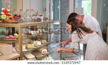 lovely girl and guy looks at different tasty cakes choosing dessert on show case shelves in modern confectionery shop #1539372947