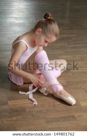 Lovely girl engaged in a pink ballet tutu and pointes in the ballet hall on the wooden dance floor
