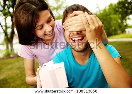 Lovely girl giving her boyfriend a present