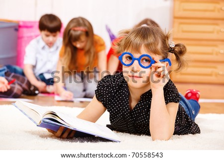 Lovely girl in glasses lying with book in hands
