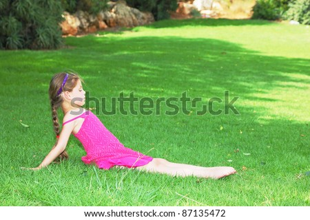 Lovely girl in pink dress shows gymnastics - stock photo