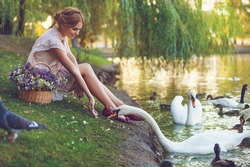 Lovely girl in retro dress and basket with flowers walks by the lake and feed a swans