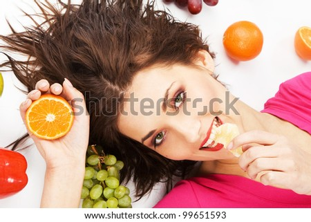 Lovely girl lying on the floor enclosed with fruits - stock photo