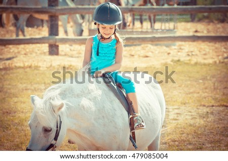 Lovely girl on a horse. Child and aimal. Litlle girl riding a horse in countryside.
