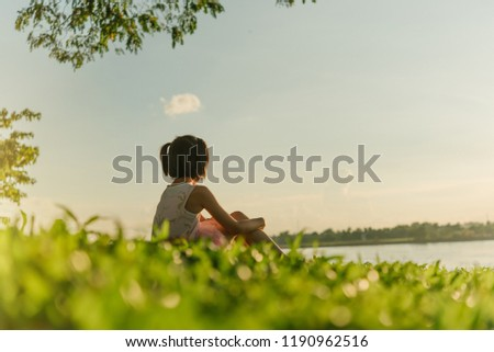 Lovely girl sitting on the water.