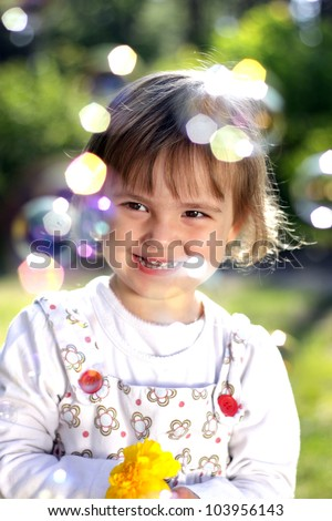 Lovely girl with a flower and soap bubbles - stock photo