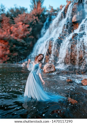 lovely girl with fair tender skin stands in aqua in long light blue dress, mystical mermaid near high waterfall with powerful streams of cold water, Lost doll with Korean face and waterproof makeup #1470117290