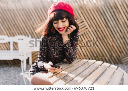 Lovely girl with short hair resting at outdoor cafe in sunny morning and checking mail in social networks. Portrait of gorgeous young french woman texting message while sitting in open-air restaurant stock photo