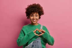 Lovely glad mixed race woman confesses in love, shapes heart gesture with hands, expresses tenderness and sympathy, true feelings wears green sweater, denim dungarees, loves boyfriend very much